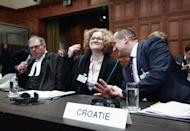 Members of the Croatian delegation, Minister Orsat Miljenic, right, Vesna Crnic-Grotic, center, and James Crawford, left, await the start of public hearings at the International Court of Justice (ICJ) in The Hague, Netherlands, Monday, March 3, 2014. Croatia is accusing Serbia of genocide during fighting in the early 1990's as the former Yugoslavia shattered in spasms of ethnic violence, in a case at the United Nations' highest court that highlights lingering animosity in the region. Croatia is asking the ICJ to declare that Serbia breached the 1948 Genocide Convention when forces from the former Federal Republic of Yugoslavia attempted to drive Croats out of large swaths of the country after Zagreb declared independence in 1991. (AP Photo/Jiri Buller)