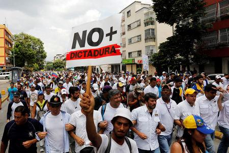 """Demonstrators take part in a rally to honour victims of violence during a protest against Venezuela's President Nicolas Maduro's government in Caracas, Venezuela, April 22, 2017. The placard reads  """"No more dictatorship"""". REUTERS/Carlos Garcia Rawlins"""