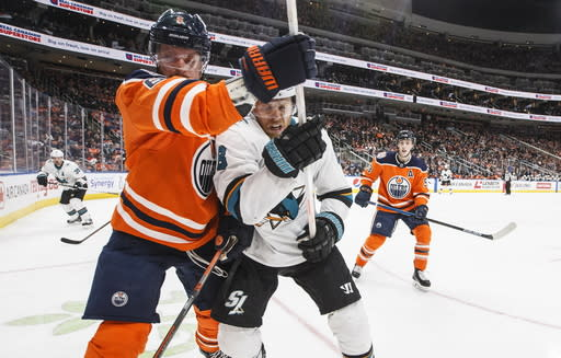 San Jose Sharks' Joe Pavelski (8) and Edmonton Oilers' Adam Larsson (6) battle near the corner during the third period of an NHL hockey game Thursday, April 4, 2019, in Edmonton, Alberta. (Jason Franson/The Canadian Press via AP)