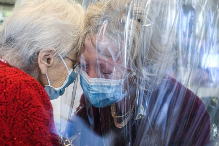 """A resident at the Domenico Sartor nursing home near Venice hugs her visiting daughter through a plastic screen in a so-called """"Hug Room"""""""