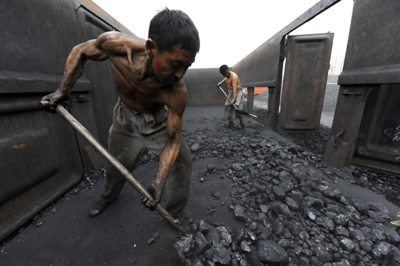 FILE PHOTO: Workers unload coal at a storage site along a railway station in Hefei,