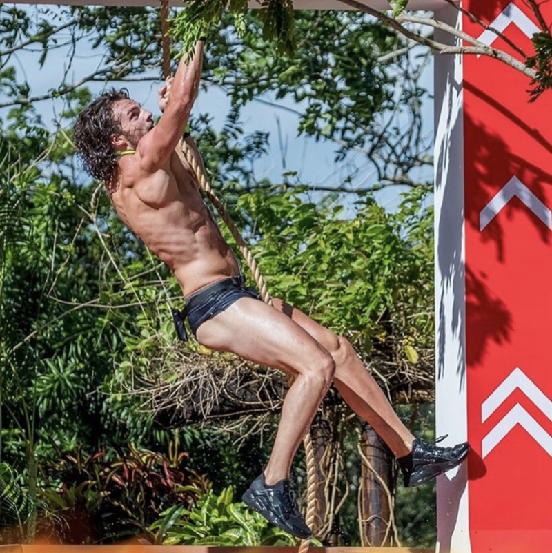 A photo of Love Island star Eoghan Murphy wearing Speedos and climbing a rope in an obstacle course.