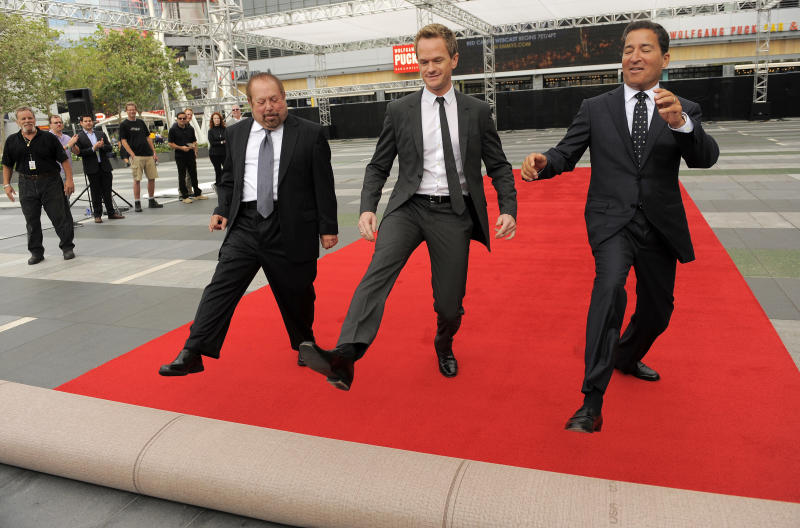 Ken Ehrlich, left, executive producer of Sunday's 65th Emmy Awards telecast, host Neil Patrick Harris, center, and Television Academy Chairman and CEO Bruce Rosenblum roll out the red carpet for the show during Emmy Awards Press Preview Day, on Wednesday, Sept. 18, 2013, in Los Angeles. (Photo by Chris Pizzello/Invision/AP)