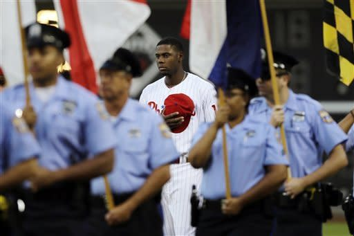 Philadelphia Phillies left fielder John Mayberry Jr., center, stands at attention as local police officers carry in the 50 state flags during a tribute to the terrorist attacks of Sept. 11, 2001, before a baseball game against the Miami Marlins, Tuesday, Sept. 11, 2012, in Philadelphia. (AP Photo/Matt Slocum)