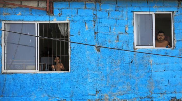 A man and a boy look out from the windows of their home during a curfew imposed by the government amid concerns about the spread of coronavirus disease, in Colombo