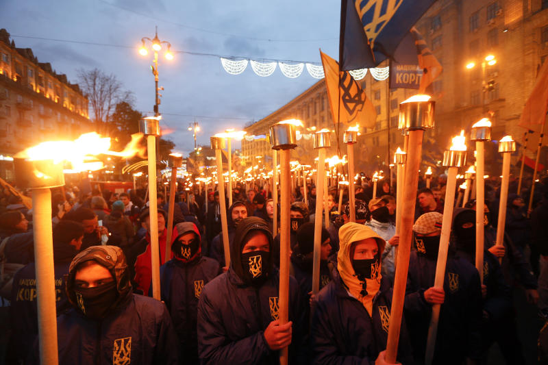 FILE - In this Saturday, Oct. 14, 2017 file photo, members of the nationalist movement carry torches during a rally marking Fatherland Defender Day in centre Kiev, Ukraine. Former Georgian President Mikhail Saakashvili, who now heads a Ukrainian opposition party, said Monday Nov. 20, 2017, he's ready to become the new prime minister, after organising a series of street protests against President Petro Poroshenko, accusing him of stalling reforms and covering up corruption.(AP Photo/Efrem Lukatsky, FILE)