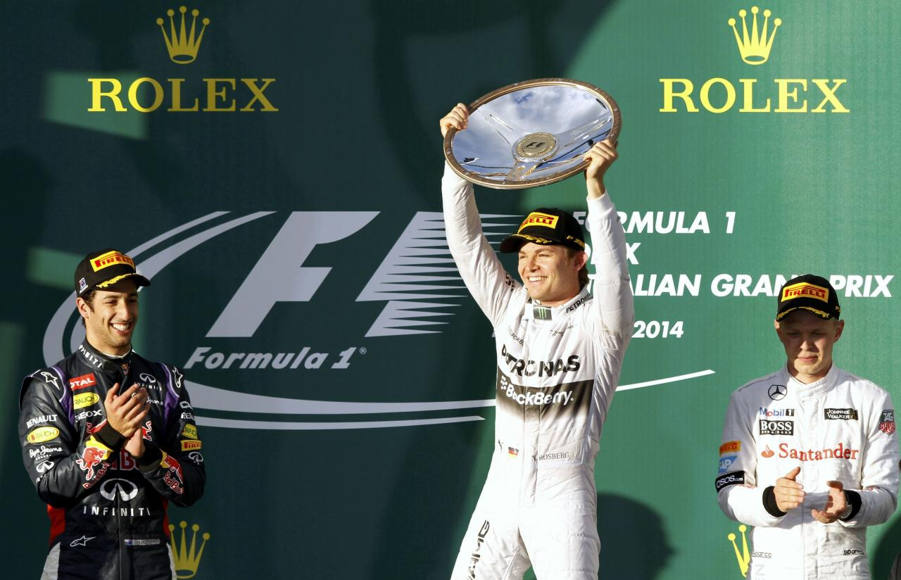 Mercedes Formula One driver Nico Rosberg of Germany (C) celebrates with his trophy on the podium as he stands beside second-placed Red Bull Formula One driver Daniel Ricciardo of Australia (L) and third-placed McLaren Formula One driver Kevin Magnussen of Denmark after the Australian F1 Grand Prix at the Albert Park circuit in Melbourne March 16, 2014. REUTERS/Brandon Malone (AUSTRALIA - Tags: SPORT MOTORSPORT F1)