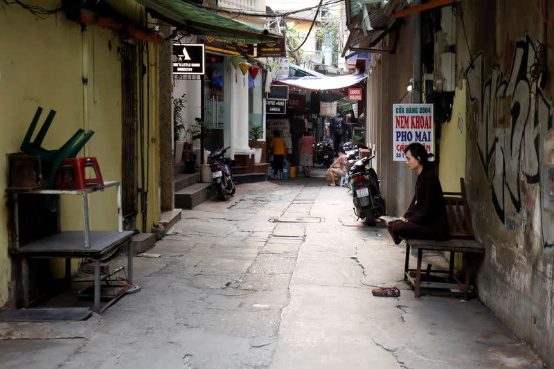 A zen practitioner sits on an empty street during the coronavirus disease (COVID-19) outbreak in Hanoi