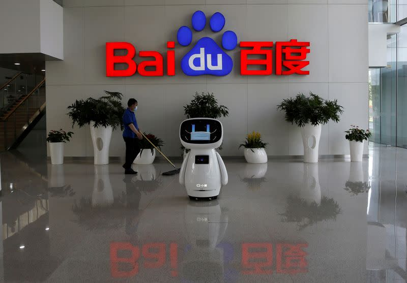 FILE PHOTO: Wworker wearing a face mask cleans the floor, near a Baidu AI robot which shows a face mask on its screen, at Baidu's headquarters in Beijing