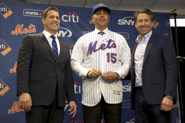 FILE - In this Nov. 4, 2019, file photo, new New York Mets manager, Carlos Beltran, center, poses for a picture with general manager Brodie Van Wagenen, left, and Mets COO Jeff Wilpon during a baseball news conference at Citi Field in New York. Beltran is out as manager of the Mets. The team announced the move Thursday, Jan. 16, 2020. (AP Photo/Seth Wenig, File)