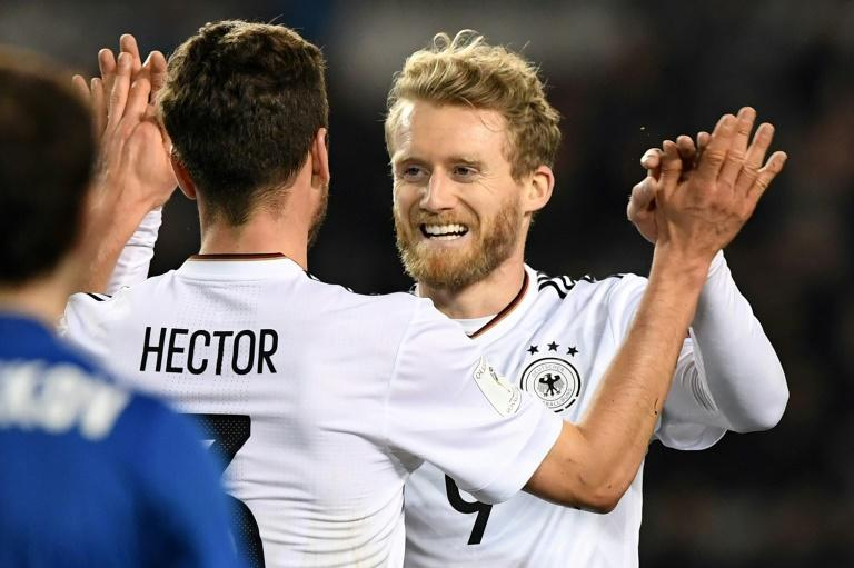 Germany's Andre Schuerrle (R) celebrates with Jonas Hector after scoring a goal against Azerbaijan on March 26, 2017