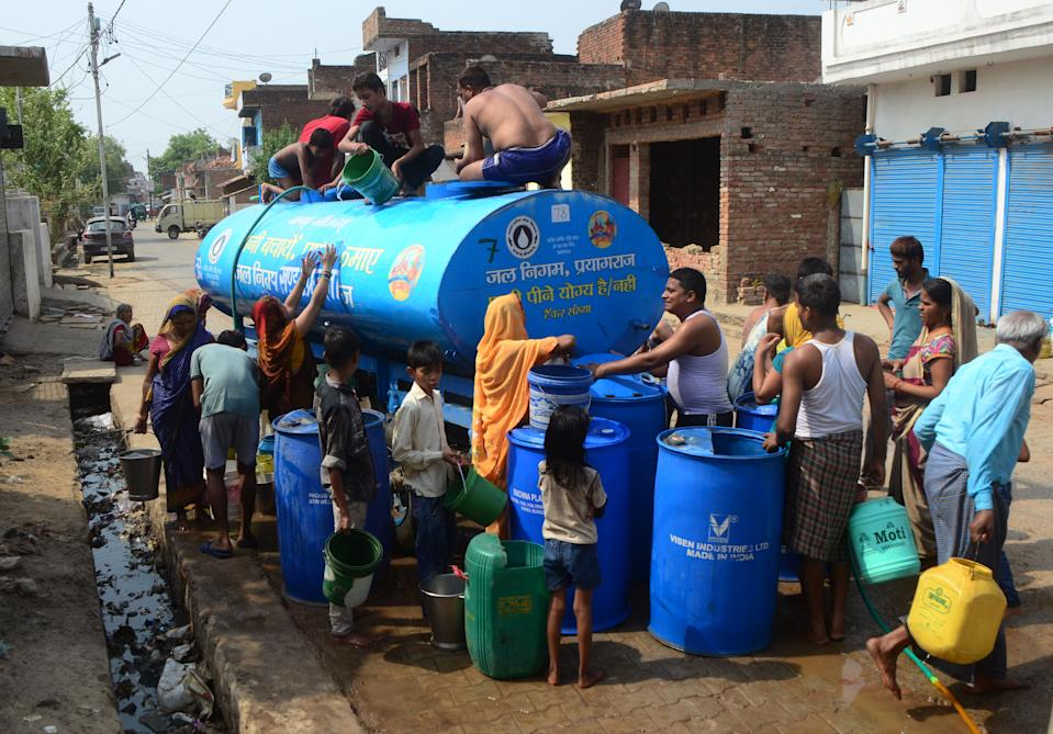 Indian local people take drinking water from a municaipal water tanker during a hot day in ShankarGarh Village , some 40 kms from Allahabad on June 6, 2019. the environmental scientist has already declared monsoon to be arriving late this year. mostly the monsoon season uses to arrive in the month of March in northeastern regions and by 15 or 16 June to central India, south India and north India. in northeastern states, the monsoon arrived in the month of May last 2019 this year and similarly in the other states it might arrive in June last .these drastic shift in climate has already resulted into climatic issues like drought especially in the north India, which is one the biggest agriculture prone area this condition worsens the condition of livelihood and farmers . which lead to unemployment, migration. a survey resulted that 10 million farmers are affected due to drought this year. around 80 % of crops have been destroyed in many places.water scarcity and crop failure resulted in declination of socio-economic condition of many states. this situation can later affect the farm distress. groundwater extraction and most importantly it will rise social (on water ) conflicts among states people farmers and also in rural areas (Photo by Ritesh Shukla/NurPhoto via Getty Images)