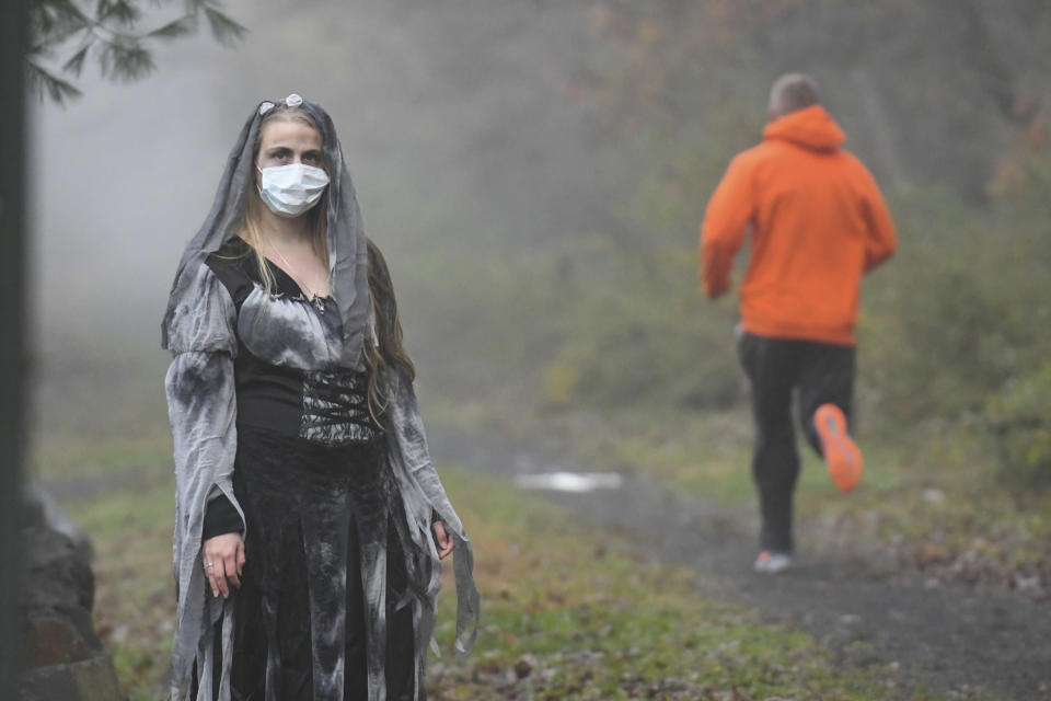 Rachel Adams, of Pottsville, Pa., portrays a zombie as a runner jogs past along the John B. Bartram trail during Schuylkill County's VISION's Spooky Schuylkill 5K Zombie Run/Walk in Landingville, Pa., on Saturday, Oct. 31, 2020. The event was held live and virtual. (Jacqueline Dormer/Republican-Herald via AP)