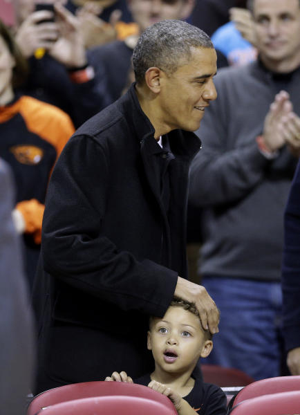 United States President Barack Obama pats a young fan on the head as he walks to his seat before an NCAA college basketball game between Maryland and Oregon State in College Park, Md., Sunday, Nov. 17, 2013. Obama's brother-in-law is Oregon State head coach Craig Robinson. (AP Photo/Patrick Semansky)