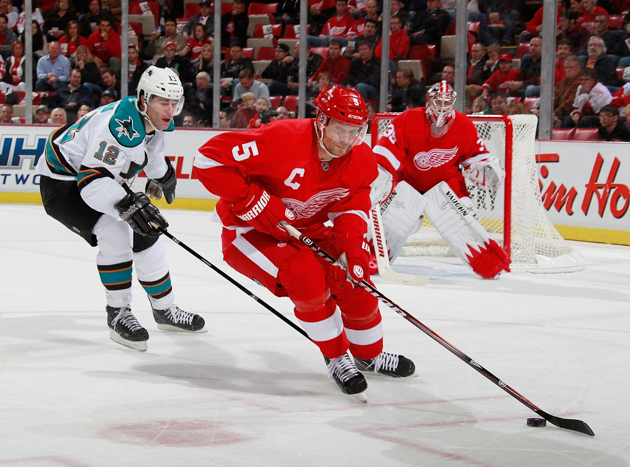 DETROIT, MI - OCTOBER 28: Nicklas Lidstrom #5 of the Detroit Red Wings tries to get around the stick of Patrick Marleau #12 of the San Jose Sharks at Joe Louis Arena on October 28, 2011 in Detroit, Michigan.  (Photo by Gregory Shamus/Getty Images)
