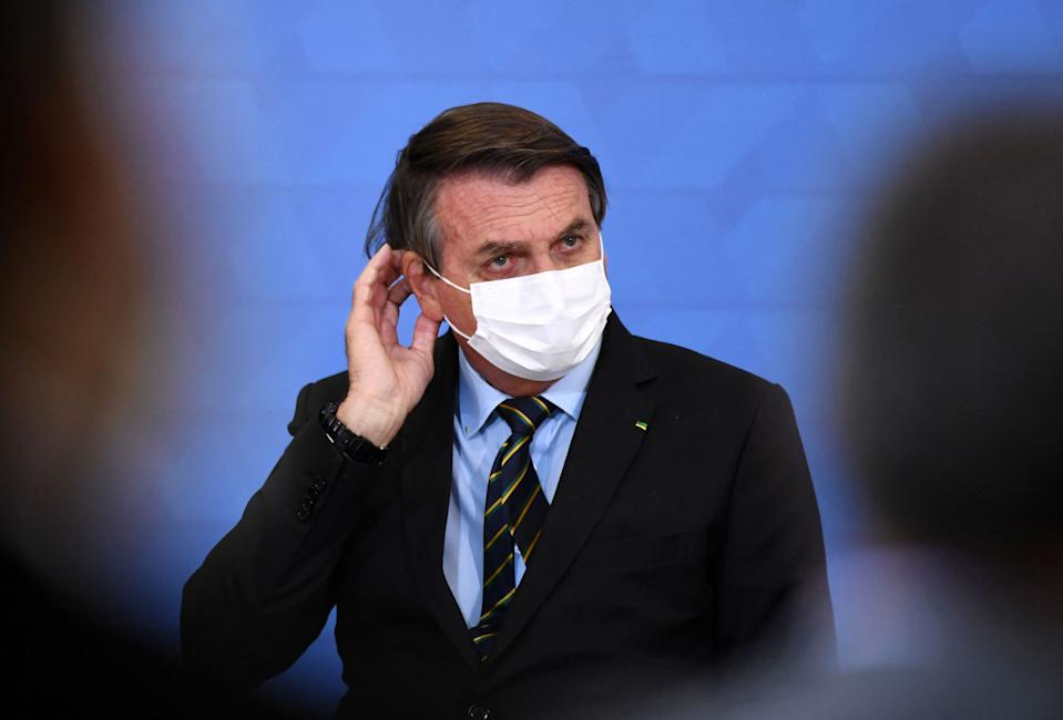 Brazilian President Jair Bolsonaro gestures as he speaks during the announcement of support measures to philanthropic hospitals in the fight against the novel coronavirus disease, COVID-19, at Planalto Palace in Brasilia, on March 25, 2021. - Brazil's death toll in the coronavirus pandemic surpassed 300,000 on March 24, as a deadly surge that has pushed hospitals to the brink made it the second country after the United States to pass the bleak milestone. (Photo by EVARISTO SA / AFP) (Photo by EVARISTO SA/AFP via Getty Images)