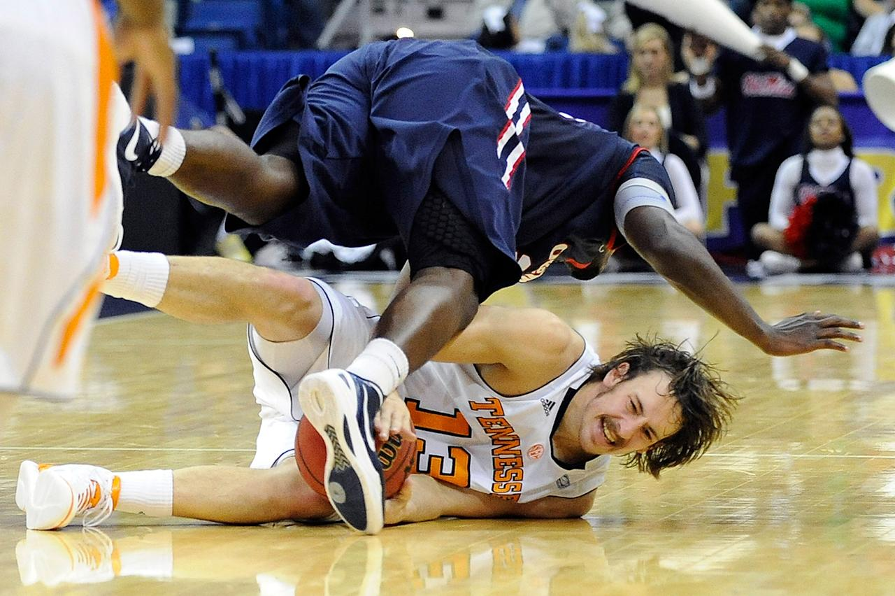 Murphy Holloway #31 of the Ole Miss Rebels trips over Skylar McBe #13 of the Tennessee Volunteers during the quarterfinals of the SEC Men's Basketball Tournament at the New Orleans Arena on March 9, 2012 in New Orleans, Louisiana.  (Photo by Stacy Revere/Getty Images)