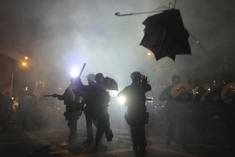 A broken umbrella flies by near riot police, during confrontation with protesters in Hong Kong Sunday, July 21, 2019. (Photo: Andy Lo/HK01 via AP)