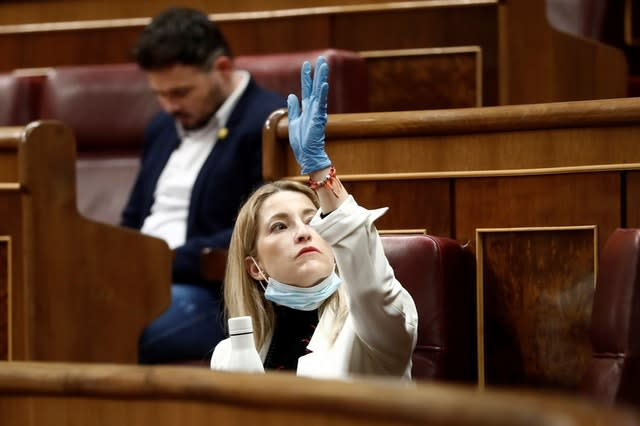 Ciudadanos party deputy Maria Munoz Vidala wearing protective gloves, gestures in a nearly empty parliament in Madrid on Wednesday, when the majority of parliamentarians follow the session online, before a vote to approve the extension of the national lockdown (Mariscal/Pool/AP)