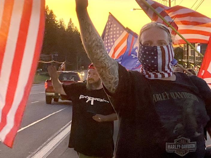Supporters of President Donald Trump and police wave flags in Sandy, Ore.