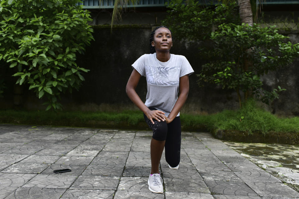 In this photo taken on Wednesday, Oct. 14, 2020, Dodeye Ewa, 16 year old work out inside her family compound in Calabar, Nigeria. The third child is bothered by President Donald Trump's rhetoric and his policies toward international students, most recently one announced Friday that limits their stays in the U.S. to two or four years with uncertainty about whether their visas will be extended. (AP Photo/Daniel H Williams )