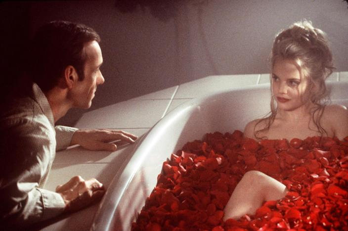 Kevin Spacey looking at Mena Suvari in a bathtub filled with roses