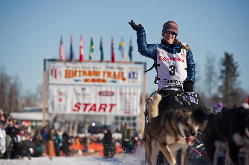 Musher Paige Drobny, of Fairbanks, waves to the crowd after she leaves the staring line of the Iditarod Trail Sled Dog Race on Willow Lake, Sunday, March 2, 2014, in Willow, Alaska. The race will take mushers nearly a thousand miles to the finish line in Nome, on Alaska's western coast. (AP Photo/Anchorage Daily News, Marc Lester)