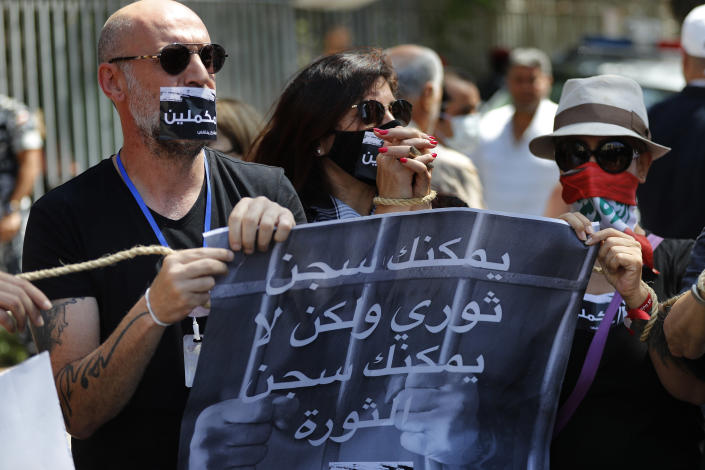 """Lebanese anti-government activists protest outside a Lebanese court, as they demand the improving judicial independence, in Beirut, Lebanon, Wednesday, June 17, 2020. A year after anti-government protests roiled Lebanon, dozens of protesters are being tried before military courts that human rights lawyers say grossly violate due process and fail to investigate allegations of torture and abuse. The Arabic placard reads:""""You can imprison a revolutionary but you cannot imprison the revolution."""" (AP Photo/Hussein Malla)"""