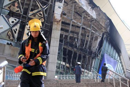 Rescue workers stand outside the site where a fire broke out at the Shanghai Hongkou soccer stadium in Shanghai, China March 28, 2017. REUTERS/Aly Song