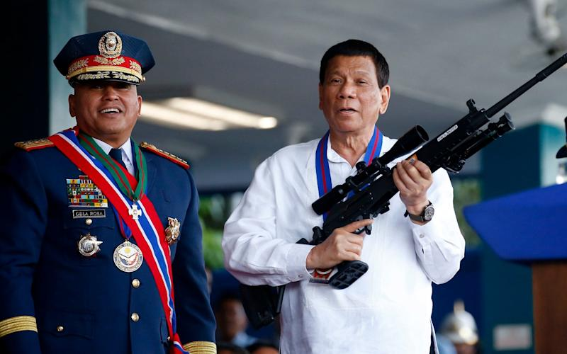 Philippine President Rodrigo Duterte holds an Israeli-made Galil rifle in April 2018 - AP