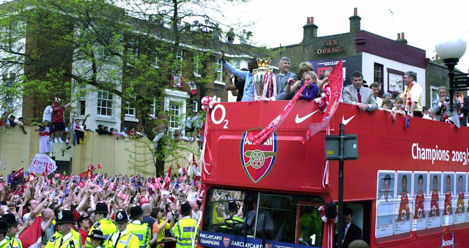 Arsenal's players and their families arrive on the open-top bus at Islington Town Hall to celebrate their title triumph (MARTYN HAYHOW/AFP/Getty Images)