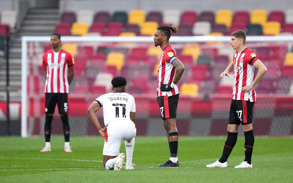 Brentford's Ivan Toney and Vitaly Janelt (right) stand as Rotherham United's Chiedozie Ogbene takes a knee prior to kick-off during the Sky Bet Championship match at the Brentford Community Stadium, London. - PA