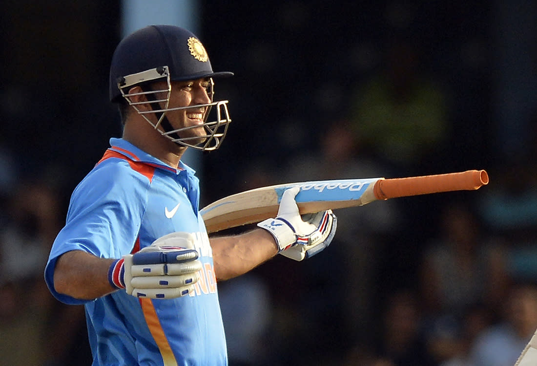 Indian cricket team captain Mahendra Sing Dhoni celebrates after hitting a boundary for six runs to seal their victory during the final match of the Tri-Nation series between India and Sri Lanka at the Queen's Park Oval stadium in Port of Spain on July 11, 2013. India defeated Sri Lanka by 1 wicket to win the series. AFP PHOTO/Jewel Samad