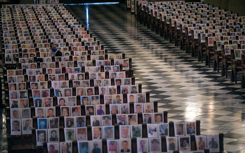 A woman sits among the more than 4 thousand portraits of people who died due to Covid-19 complications, at the Cathedral, in Lima - AP