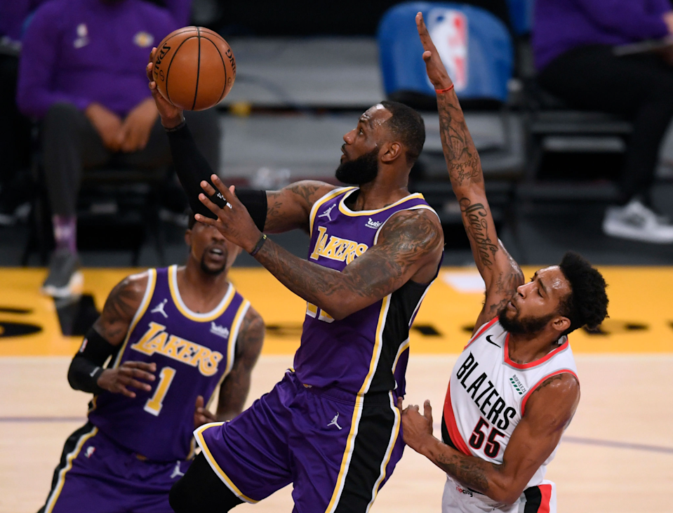 Lakers star LeBron James scores on a layup in front of Portland's Derrick Jones Jr.
