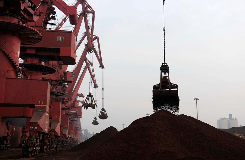 FILE PHOTO: Cranes unload iron ore from a ship at a port in Rizhao