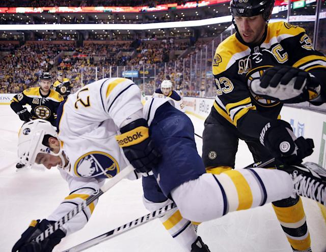 Boston Bruins' Zdeno Chara (33) and Buffalo Sabres' Matt D'Agostini (27) battle along the boards during the first period of an NHL hockey game in Boston, Saturday, April 12, 2014. (AP Photo/Michael Dwyer)