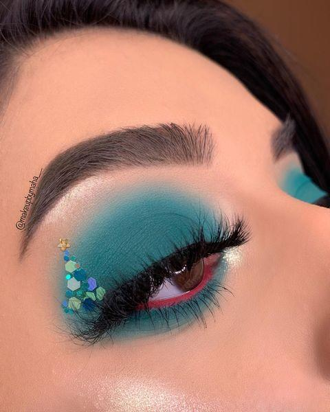 """<p>Pair bold shadow on top and bottom lids with a glitter cluster in the shape of a tree (with a teeny, tiny star on top!). Line the inside of the lower lid with a contrasting color, if desired.</p><p><a class=""""link rapid-noclick-resp"""" href=""""https://www.amazon.com/SIQUK-Stickers-Temporary-Festival-Carnival/dp/B07R5Q6B34/?tag=syn-yahoo-20&ascsubtag=%5Bartid%7C10050.g.34534998%5Bsrc%7Cyahoo-us"""" rel=""""nofollow noopener"""" target=""""_blank"""" data-ylk=""""slk:SHOP FACE GEMS AND GLITTER"""">SHOP FACE GEMS AND GLITTER</a></p><p><a href=""""https://www.instagram.com/p/B6kMNhopRNk/?utm_source=ig_embed&utm_campaign=loading"""" rel=""""nofollow noopener"""" target=""""_blank"""" data-ylk=""""slk:See the original post on Instagram"""" class=""""link rapid-noclick-resp"""">See the original post on Instagram</a></p>"""