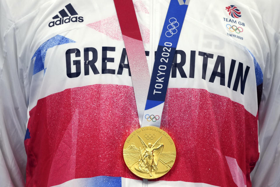 Tom Dean of Britain gold medal hangs as he stands on the podium after winning the men's 200-meter freestyle at the 2020 Summer Olympics, Tuesday, July 27, 2021, in Tokyo, Japan. (AP Photo/Matthias Schrader)