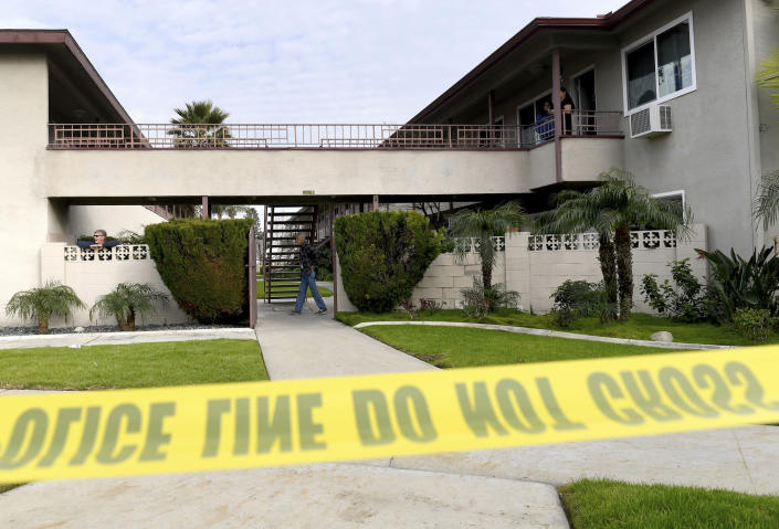 Residents mill about as Upland police investigate the scene, where police say a mother threw her young son from the second-story balcony of an apartment complex and then jumped herself as police arrived, in Upland, Calif., on Tuesday, Feb. 26, 2019. Police made a safety check of the second-story apartment and found the woman's approximately 7-month-old daughter inside. Her breathing was restored but she died at a hospital. (Jennifer Cappuccio Maher/The Orange County Register via AP)