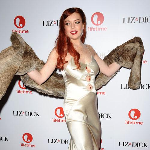 Perhaps Lohan realized her style snafu and tried to cover up. That could be the only reason why she would have a hideous fur stole on her arms. (Photo by Jason LaVeris/FilmMagic)