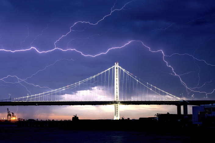 FILE - In this Aug. 16, 2020, file photo, lightning forks over the San Francisco-Oakland Bay Bridge as a storm passes over Oakland, Calif. Numerous lightning strikes sparked brush fires throughout the region. (AP Photo/Noah Berger, File)