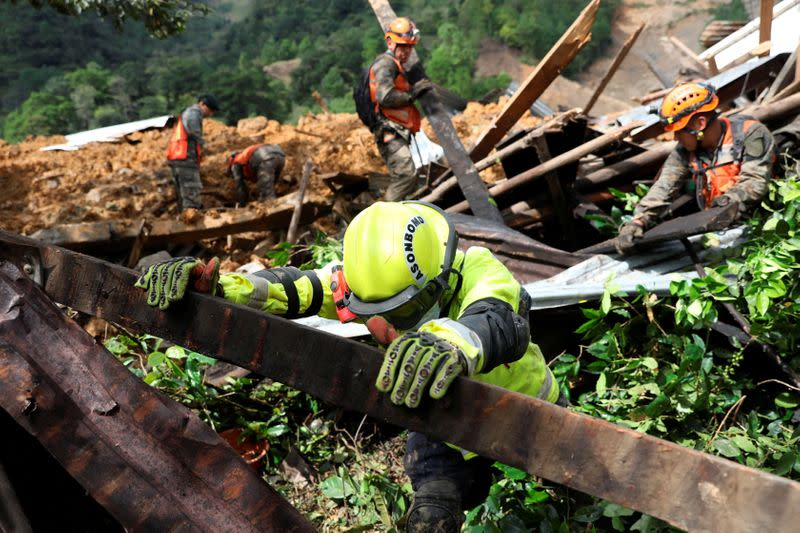 Soldiers and a firefighter remove debris from an area hit by a mudslide, caused by heavy rains brought by Storm Eta, as the search for victims continue in the buried village of Queja