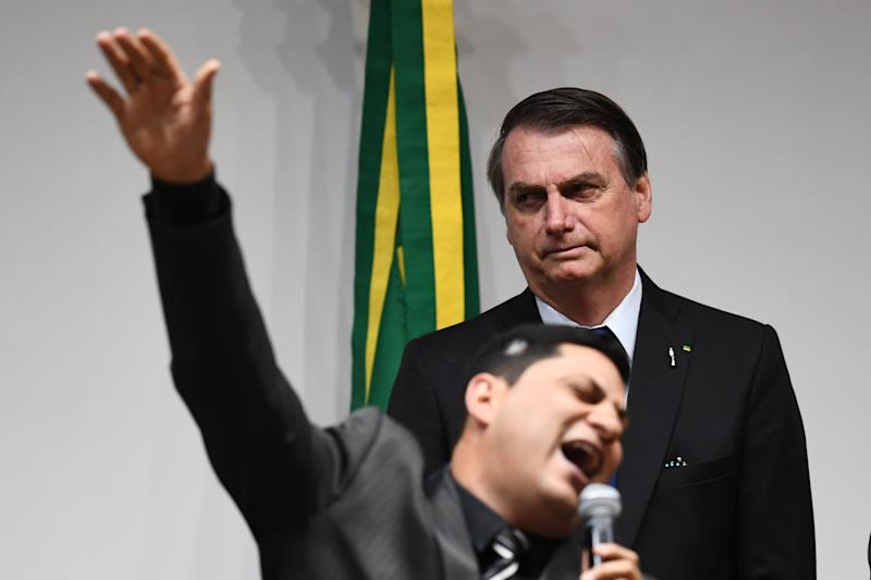 Brazilian President Jair Bolsonaro (behind) listens as an evangelical pastor speaks before deputies vote a pension reform bill at the National Congress in Brasilia, on July 10, 2019. - After several delays and amendments, pro-government deputies are working to get the necessary approval to pass a pension reform bill to the Senate before the Congress's mid-year recess. (Photo by EVARISTO SA / AFP) (Photo credit should read EVARISTO SA/AFP via Getty Images)