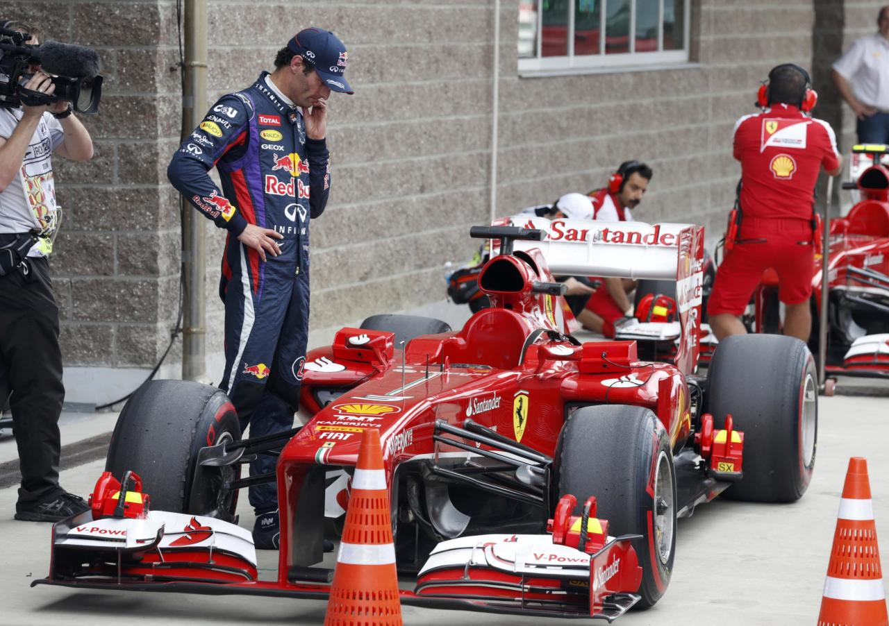 Red Bull Formula One driver Mark Webber of Australia looks at the car of Ferrari Formula One driver Fernando Alonso of Spain after the qualifying session for the Korean F1 Grand Prix at the Korea International Circuit in Yeongam, October 5, 2013. REUTERS/Lee Jae-Won (SOUTH KOREA - Tags: SPORT MOTORSPORT F1)