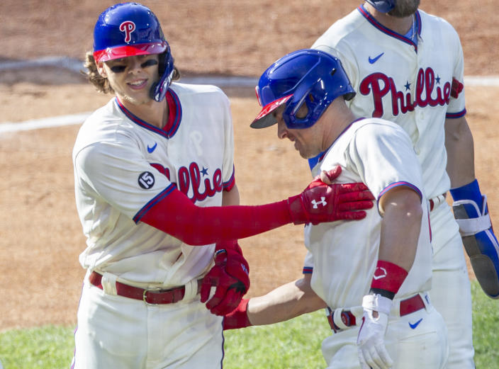 Philadelphia Phillies Alec Bohm, left, is congratulated by J.T. Realmuto after he hit a home run during the first inning of a baseball game against the New York Mets, Wednesday, April 7, 2021, in Philadelphia. (AP Photo/Laurence Kesterson)