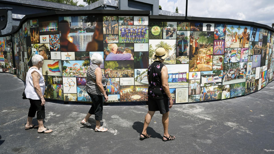 Visitors pay tribute to the outdoor display at the Pulse nightclub memorial Friday, June 11, 2021, in Orlando, Fla. Saturday will mark the fifth anniversary of the mass shooting at the site.(AP Photo/John Raoux)