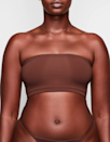 """<p><strong>Key selling points:</strong> If you're searching for a true """"second skin"""" feel, consider the Fits Everybody Bandeau from <a href=""""https://www.glamour.com/story/skims-nordstrom-launch?mbid=synd_yahoo_rss"""" rel=""""nofollow noopener"""" target=""""_blank"""" data-ylk=""""slk:Kim Kardashian's shapewear line"""" class=""""link rapid-noclick-resp"""">Kim Kardashian's shapewear line</a>, Skims. The smooth bandeau stretches across curves with zero cutting and complete comfort, and is available in an inclusive range of skin tones and sizes.</p> <p><strong>What customers say:</strong> """"I am a 34D and am always looking for something with support that's not going to be corset-like. My current strapless bra is so tight that I couldn't do it anymore. So I decided to try this and I'm <em>obsessed</em>. It's supportive, gives you a nice smooth back in any top you wear and is so comfortable. The material is like butter! I can't wait to buy more."""" —<em>Brianna B., reviewer on</em> <a href=""""https://fave.co/3hqf4Ud"""" rel=""""nofollow noopener"""" target=""""_blank"""" data-ylk=""""slk:Skims"""" class=""""link rapid-noclick-resp""""><em>Skims</em></a></p> $28, Skims. <a href=""""https://skims.com/products/fits-everybody-bandeau-bra-cocoa"""" rel=""""nofollow noopener"""" target=""""_blank"""" data-ylk=""""slk:Get it now!"""" class=""""link rapid-noclick-resp"""">Get it now!</a>"""