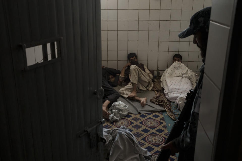 A Taliban fighter talks to detainees at a police station in Kabul, Afghanistan, Sunday, Sept. 19, 2021. The Taliban are shifting from being warriors to an urban police force. (AP Photo/Felipe Dana)