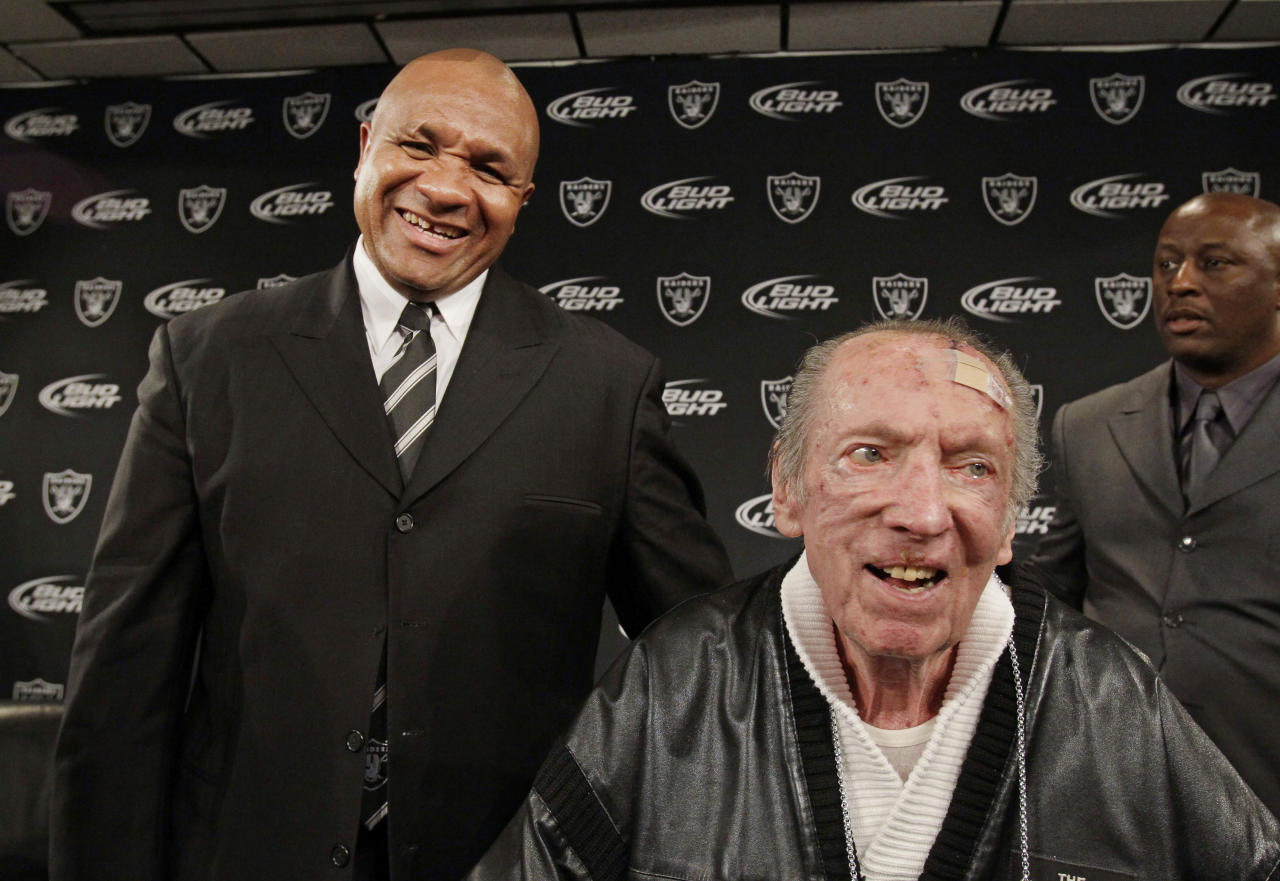 FILE - In this Jan. 18, 2011 file photo shows new Oakland Raiders head coach Hue Jackson, left, and Oakland Raiders owner Al Davis, right, smile at a news conference at NFL football Raiders headquarters in Alameda, Calif. The Oakland Raiders announce Saturday, Oct. 8, 2011, that longtime owner and Hall of Famer Al Davis has died. He was 82. (AP Photo/Paul Sakuma, File)